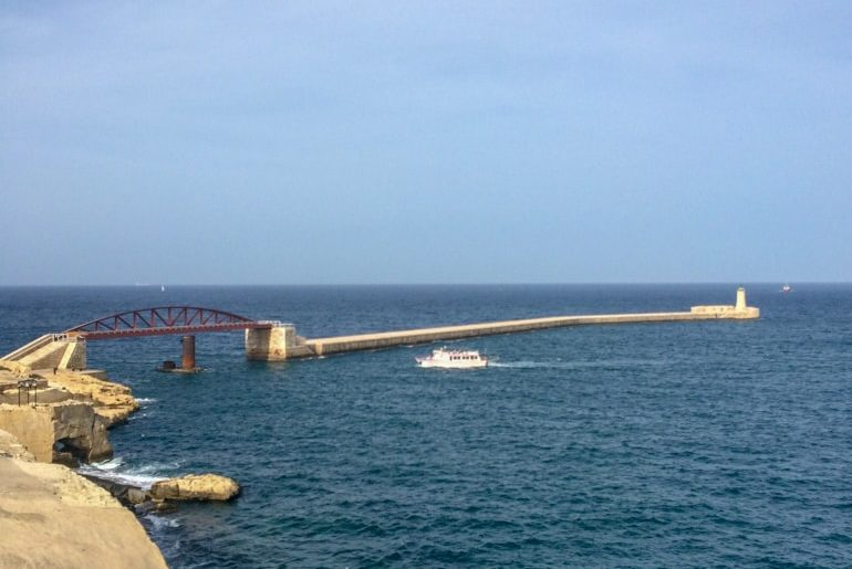 red iron bridge with long pier and blue ocean things to do in valletta