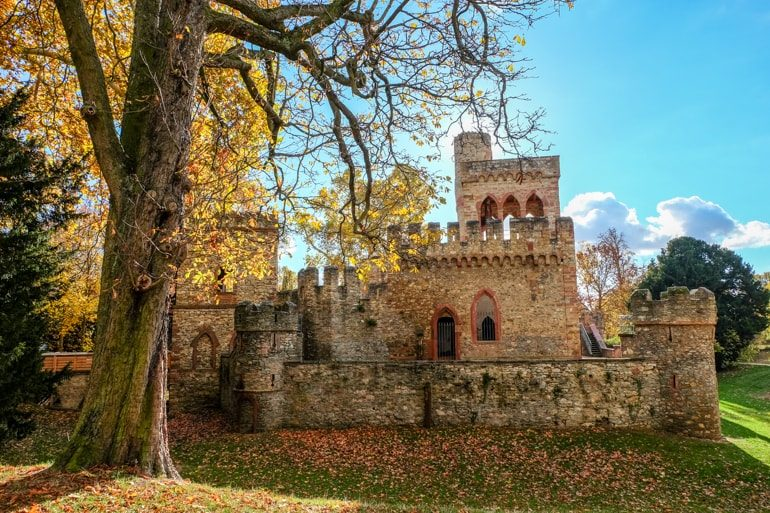 small stone castle with blue sky and autumn tree in front things to do in wiesbaden