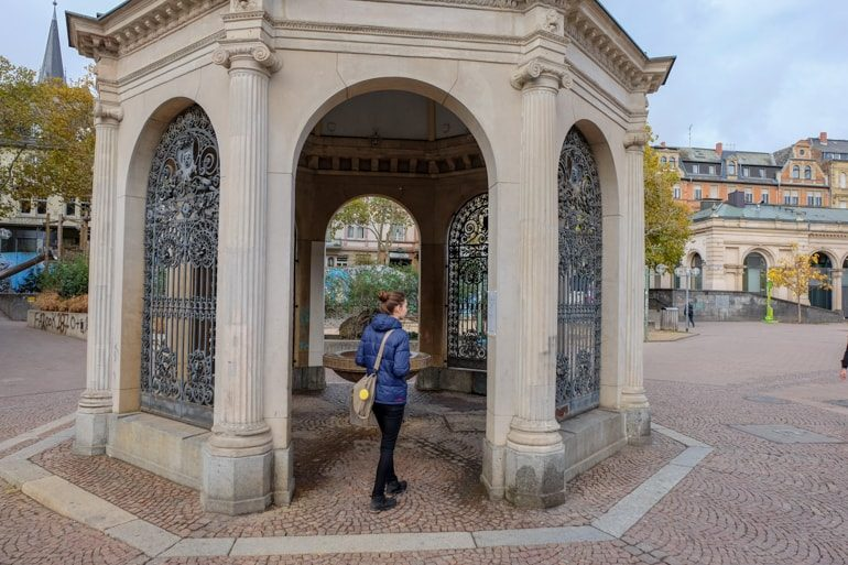 girl in blue jacket standing in entrance to arched stone tower things to do in wiesbaden