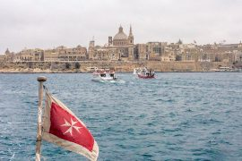 maltese flag with boats in water and city in background travelling to malta