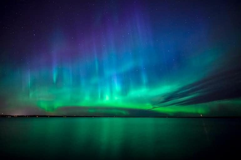 northern lights colour shining above lake experiences of a lifetime