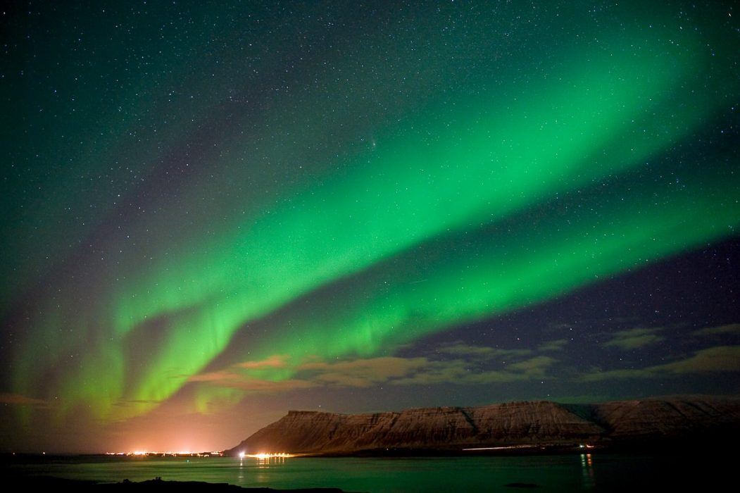 green lights over lit up city and mountain trips to see the northern lights iceland