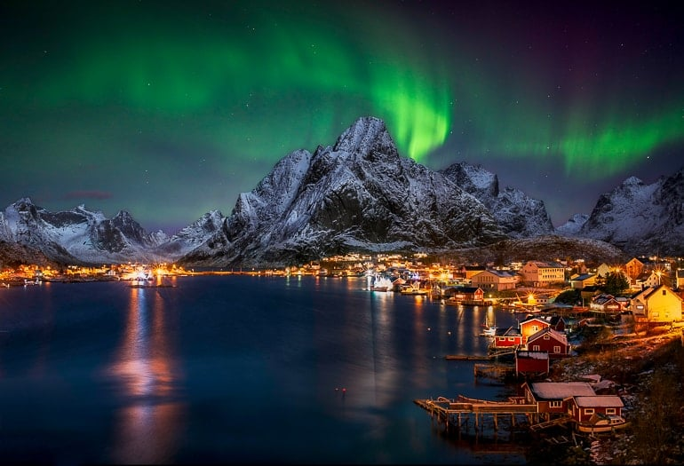 coastal city lit up at night with mountain and northern lights in norway