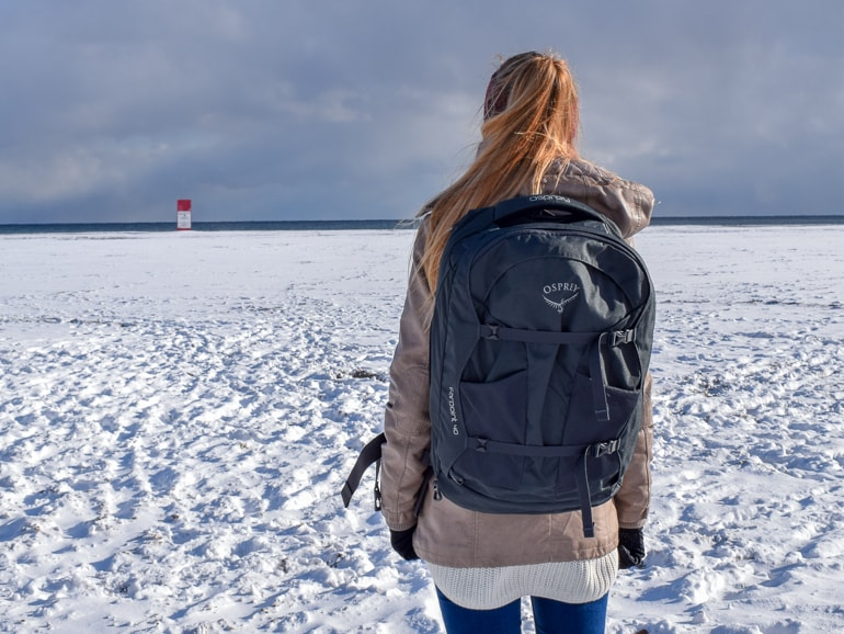 girl with backpack standing on snowy field trips to see the northern lights packing tips