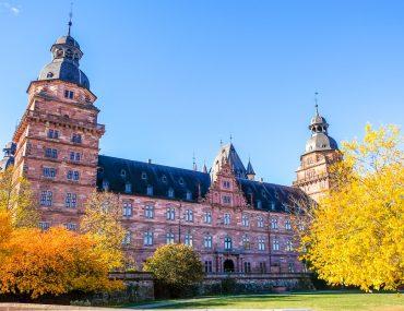 Rotes Schloss von Aschaffenburg mit Bäumen in Herbstfarben im Vordergrund