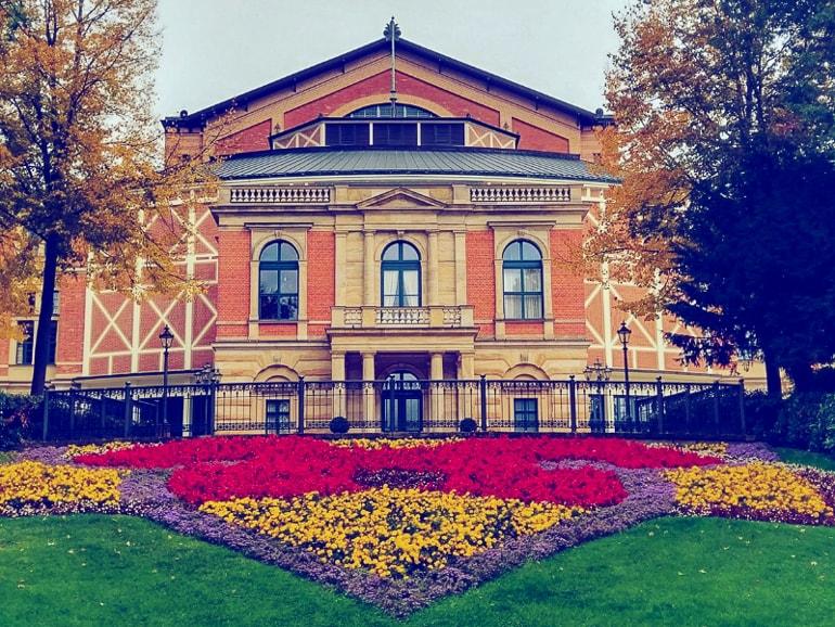 Haus mit roter Fasade und blumen und gras im Vordergrund Bayreuth schöne Städte