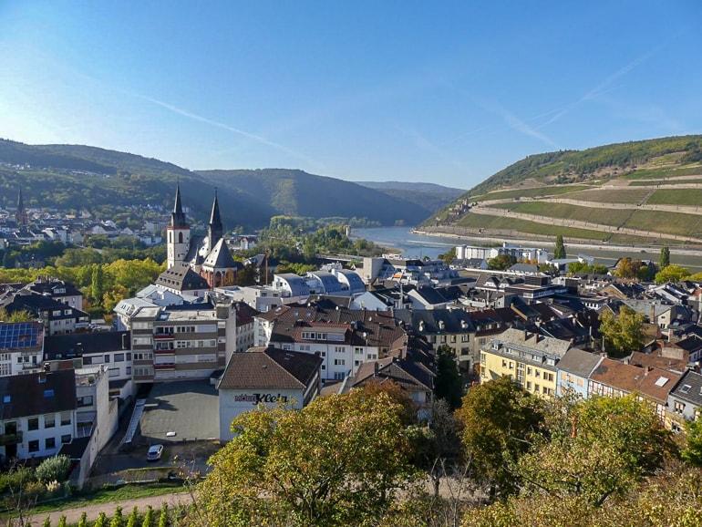 Blick auf Häuser und Kirchtürme mit Bäumen und Hügeln im Hintergrund Bingen