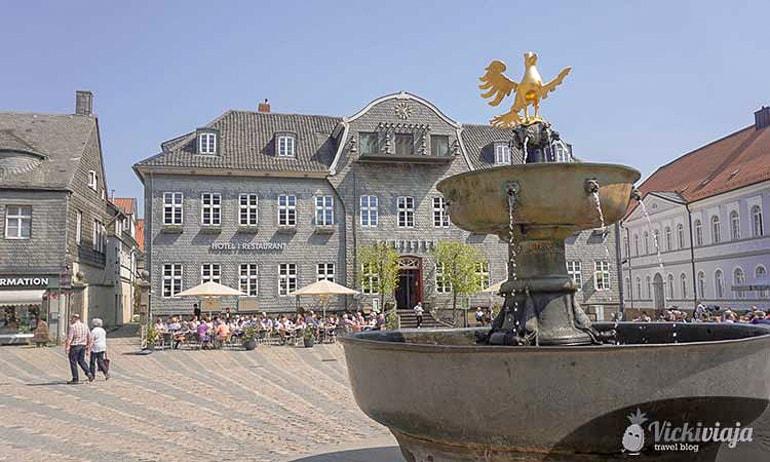 Springbrunnen mit goldenem Vogel und Gebäuden im Hintergrund Goslar schöne Städte
