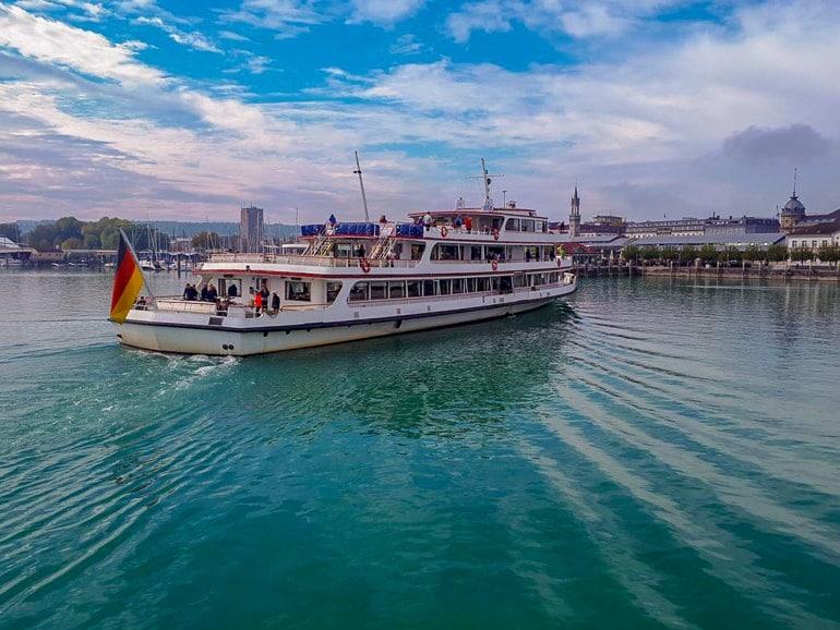 Aussichtsboot mit Deutschlandflagge auf Bodensee mit Häusern im Hintergrund Konstanz