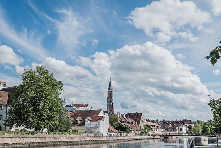 Wasser und blauer Himmel mit Häusern und Kirchturm im Hintergrund Landshut schöne Städte Deutschland