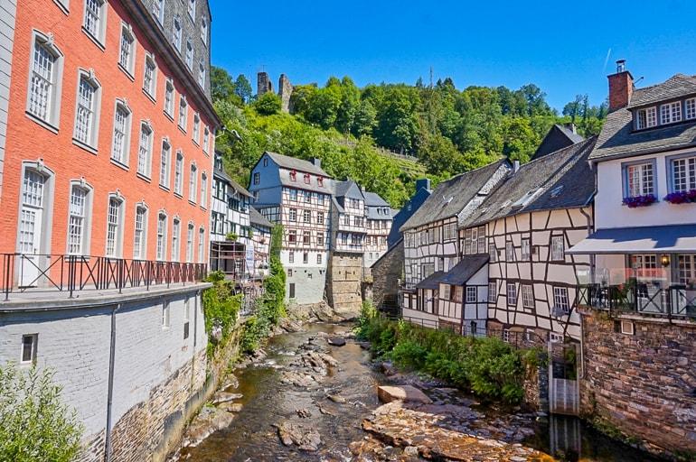 Bunte Fachwerkhäuser und Fluss mit Bäumen im Hintergrund Monschau schöne Städte