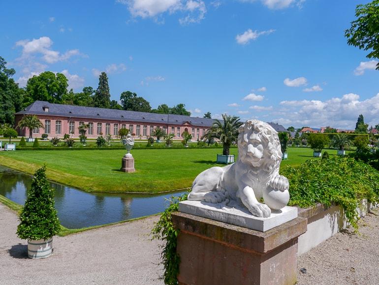 Löwenstatue mit grünem Gras und Gebäude im Hintergrund Schwetzingen Deutschland