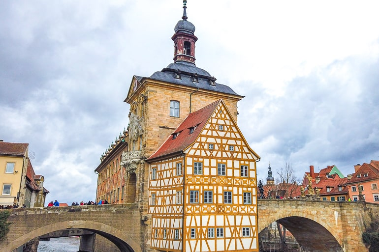 yellow wooden town hall connected to bridge in bamberg germany