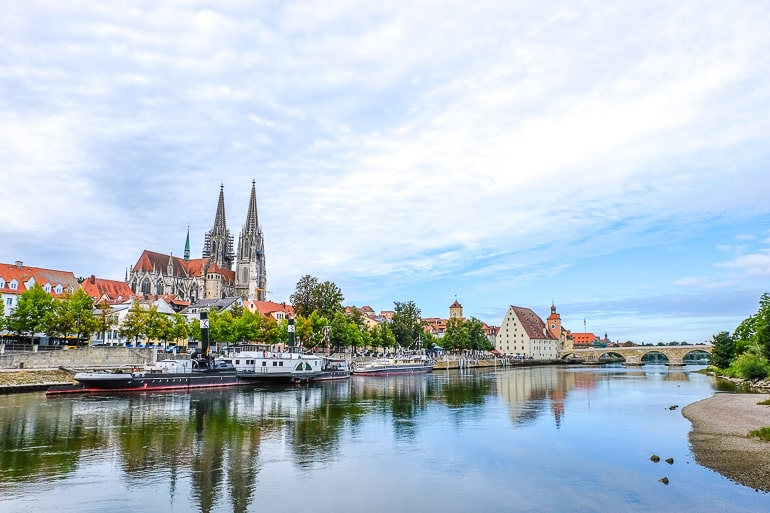 river with boats and bridge over it with cathedral behind in regensburg germany