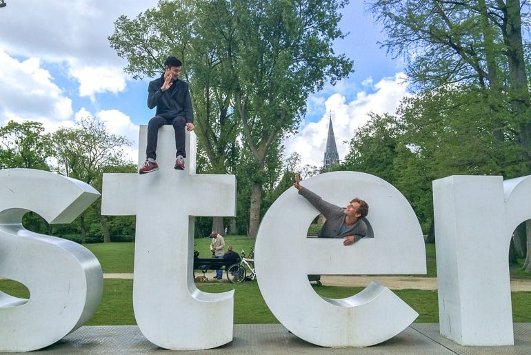 two guys waving from large white letters european hostels amsterdam netherlands