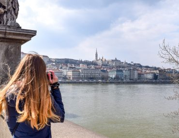 blonde girl with camera taking photo of castle and river european hostels budapest hungary
