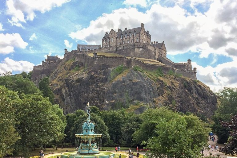 castle on top of green hill with fountain european hostels edinburgh scotland