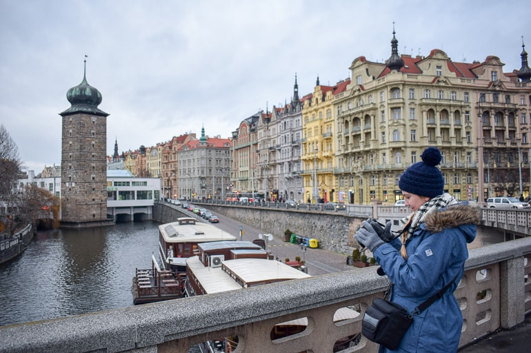 girl in winter hat taking photo of old town buildings european hostels prague czech republic