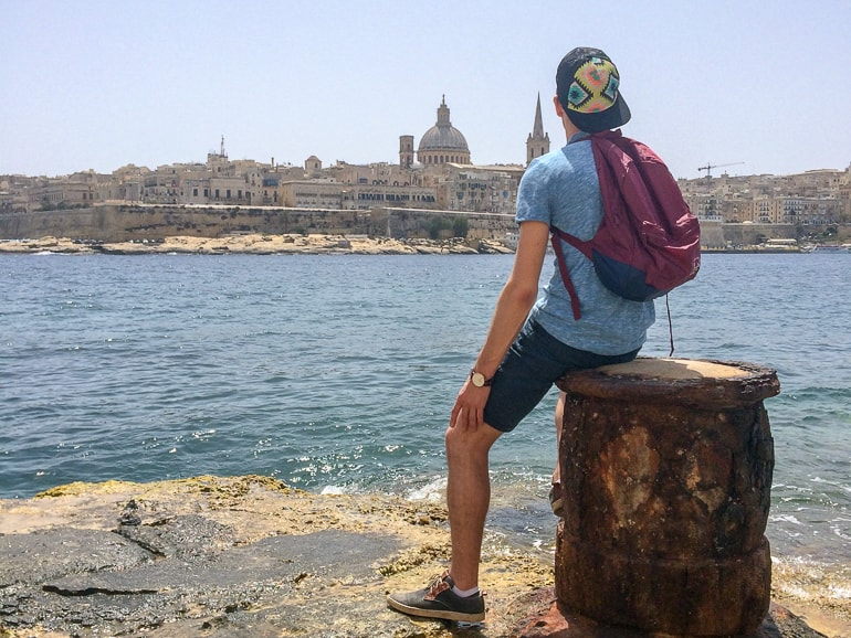 man with hat and backpack sitting on pier looking over harbour european hostels sliema malta