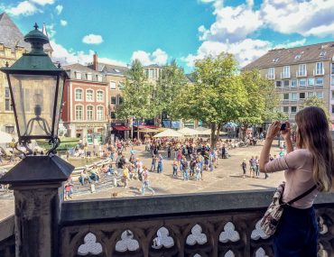 girl taking photo of german square hostels in germany