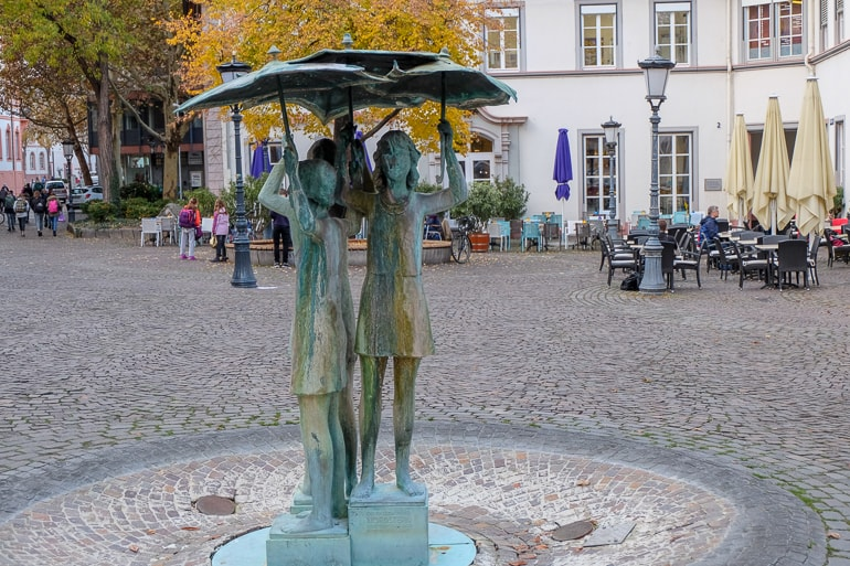 metal fountain of girls with umbrellas in square things to do in mainz germany