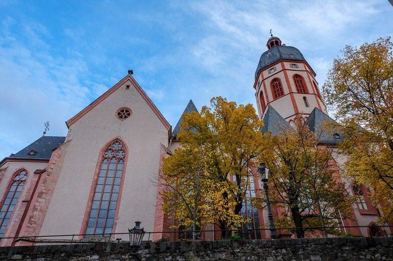 Bunte Fasade von Kirche mit Glasfenster und grünen Bäumen Mainz