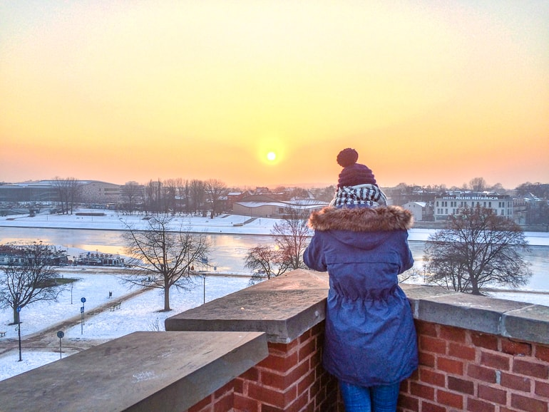 orange sunset and girl in winter hat where to stay in krakow wawel castle