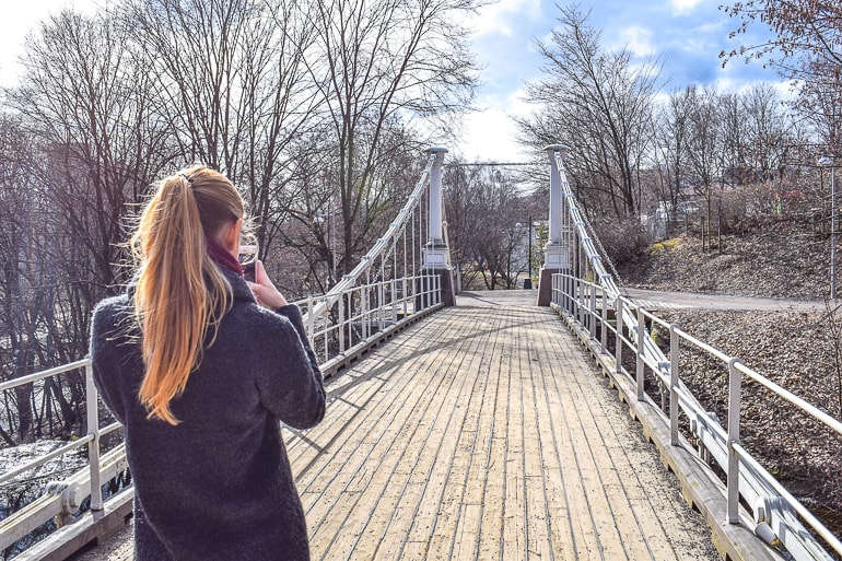 girl taking photo of wooden bridge where to stay in oslo