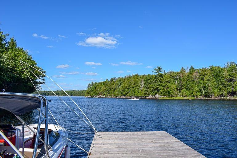 Steg aus Holz mit Boot und blauem See Ontario Kanada