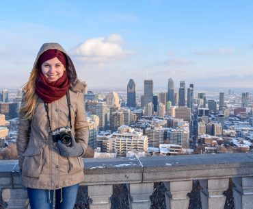 girl in winter coat with city behind canada packing list