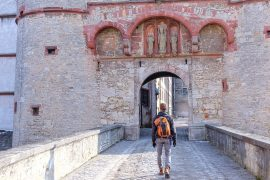 boy with backpack walking into old castle travelling to europe for the first time