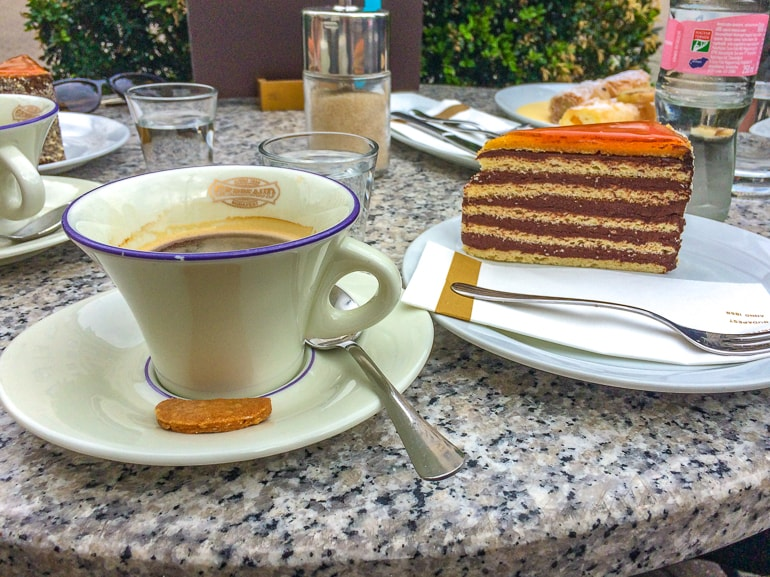 coffee in mug with slice of cake on table one day in budapest