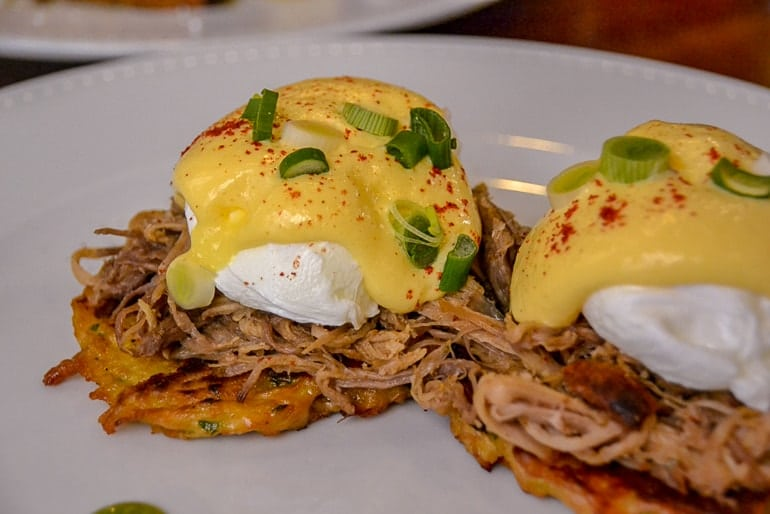 pulled pork eggs benedict on white plate one day in budapest