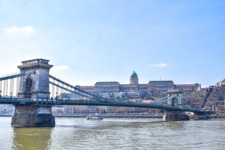 large bridge over river with boat castle behind one day in budapest