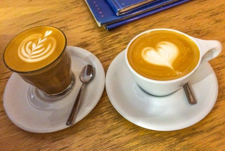 two coffees with latte heart art on wood table one day in budapest