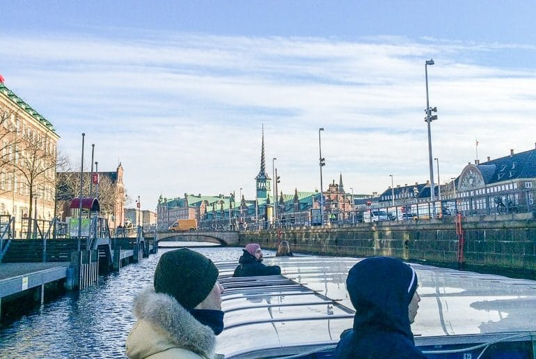 people on flat boat looking at city one day in copenhagen
