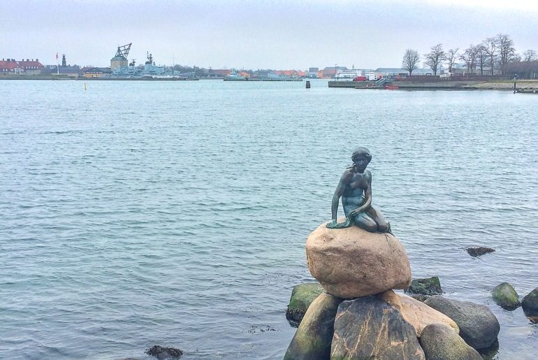 mermaid statue on rock with water behind one day in copenhagen