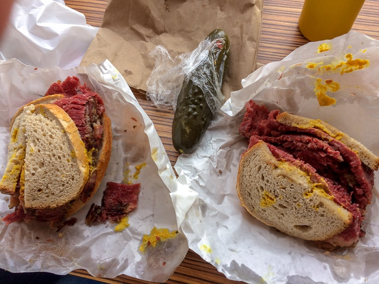 smoked meat sandwiches on table with pickle schwartz deli montreal