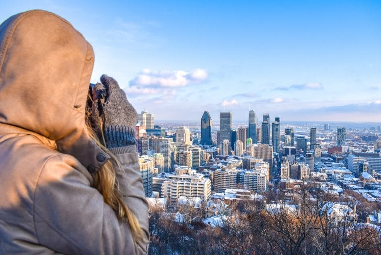 girl with jacket taking photo of skyscrapers below montreal