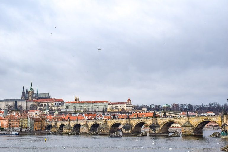 long bridge over riv er leading to castle on hill one day in prague