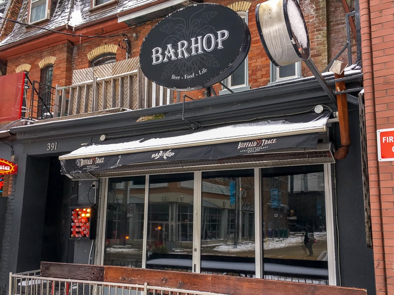 bar sign and front patio from sidewalk one day in toronto