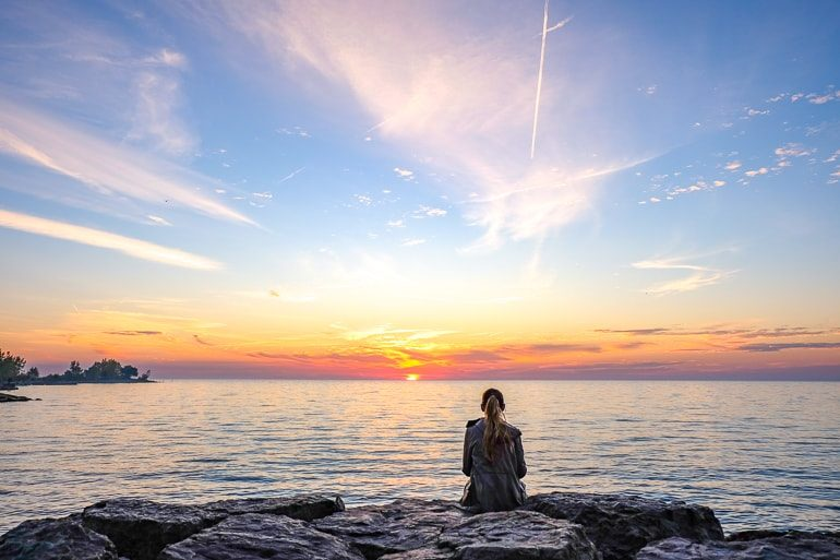 girl sitting on rocks with sunrise behind over lake one day in toronto
