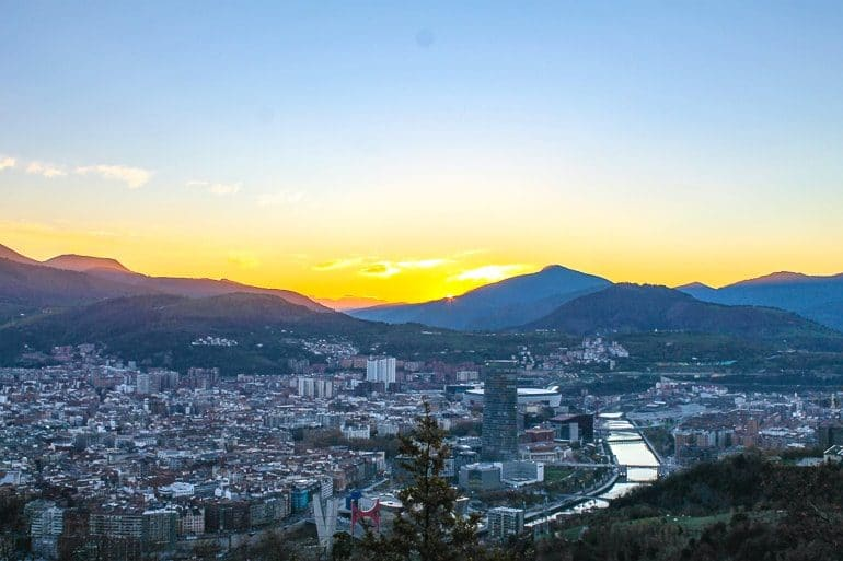 city with river and sunset over mountains behind things to do in bilbao spain