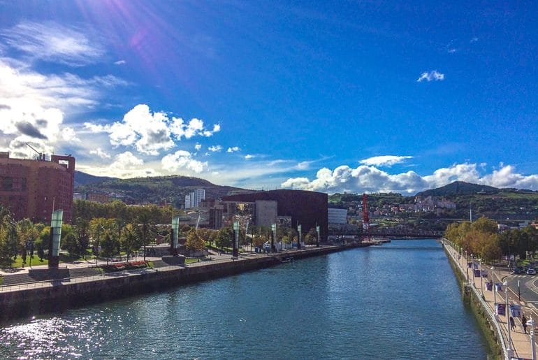 river splitting a city centre with blue sky things to do in bilbao spain