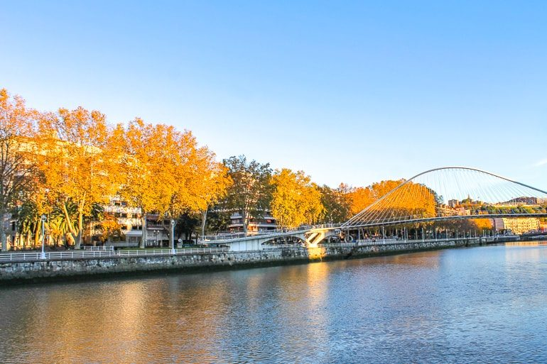 curved bridge over river with fall leaves things to do in bilbao spain