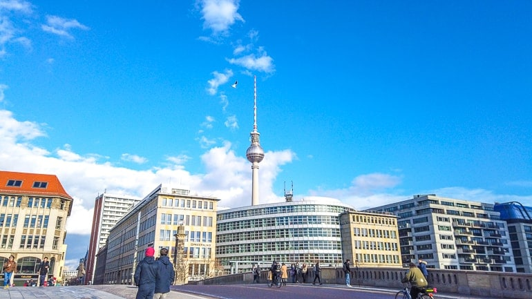tv tower rising above city buildings with blue sky berlin
