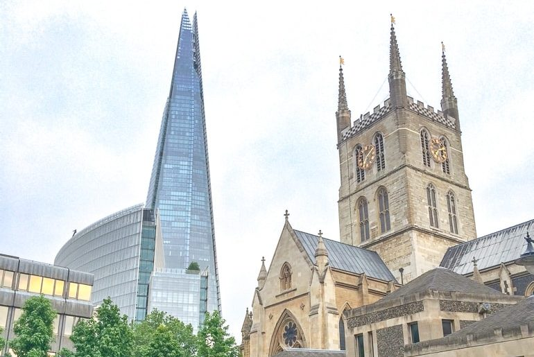 tall glass building with old church in foreground shard london attraction