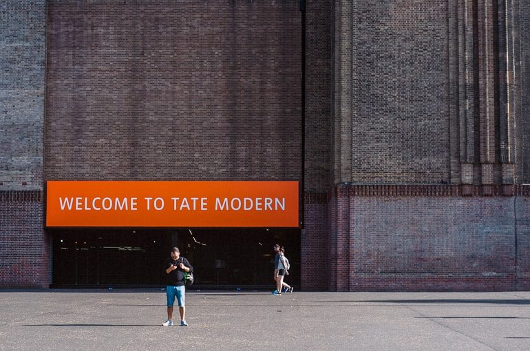red brick museum entrance with orange sign and person walking tate modern