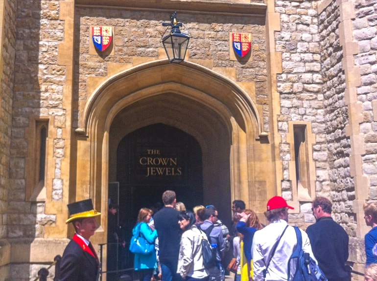 people standing in line waiting to enter crown jewels entrance tower of london attractions
