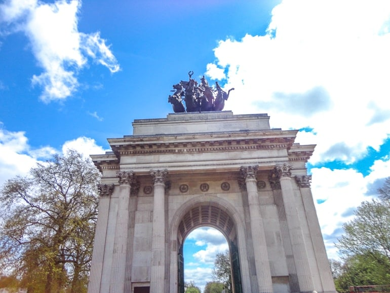 stone archway with statue on top and blue sky hyde park london